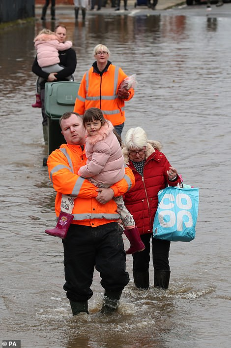Andrew Hall carries his six year-old daughter Lillie-Mai through floodwater in Doncaster,