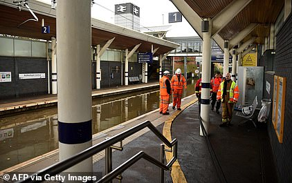 Workers inspect flooded rail tracks at Rotherham Central today