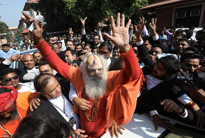 The Supreme Court of India ruled today in favor of a Hindu group in a long-standing battle over a centuries-old religious site, also claimed by Muslims. Pictured: Nirmohi Akhara leader, Dharam Das (center) and other people make gestures when they leave the scene after the announcement