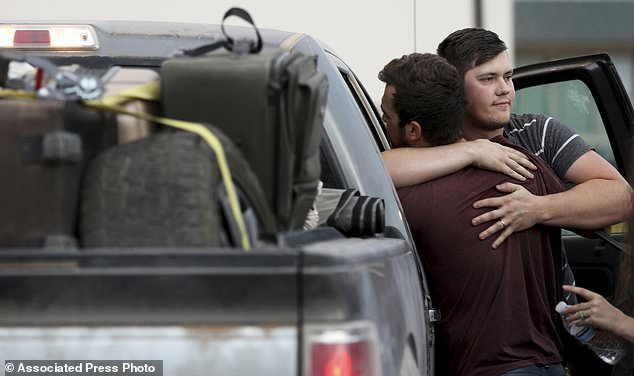 Cole Langford, left, and Hayden Spenct, of the Mormon colony in La Mora, Mexico, hug during a rendezvous in a gas station in Douglas, Arizona