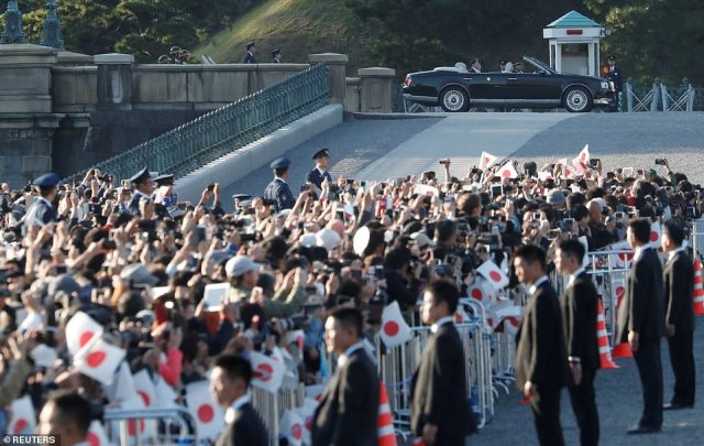 People cheer and try to take photographs from an enclosed area as they see the motorcade approaching, on November 10