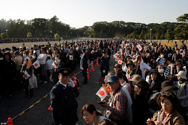 Spectators are pictured leaning over and tilting their heads to get a closer look for the arrival of Emperor Naruhito. They anticipate the start of the parade and hold Japanese flags