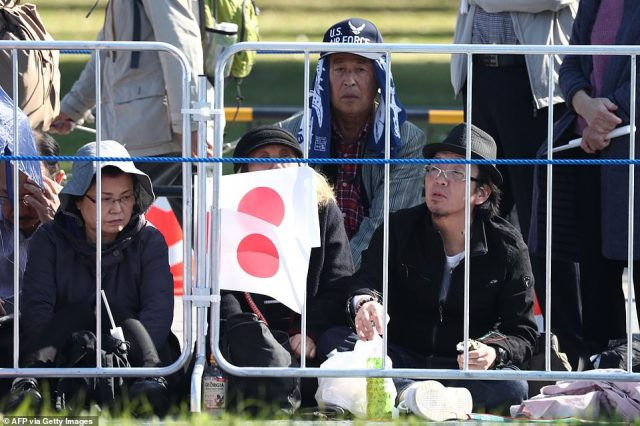 People sit patiently, while wearing sun hats, behind railings as they wait forEmperor Naruhito and Empress Masako, on November 10