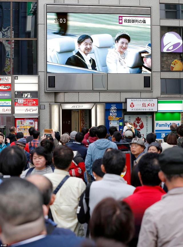 People take a moment out of their day to gather and watch the royal parade from a screen in Osaka, western Japan. They appear mesmerised as they watch the event which attracted more than 100,000 people