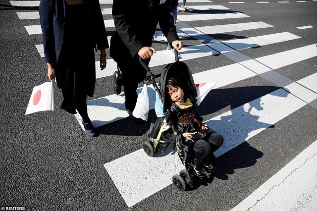 Parents, who are equipped with a national Japanese flag, head to the royal parade with their daughter having a doze in a push chair