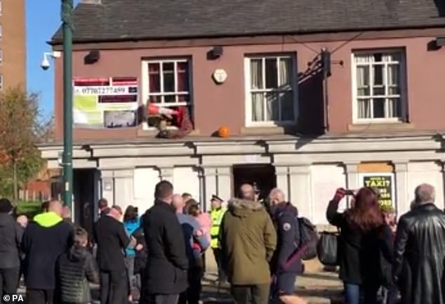 As he goes back inside the disused pub, someone in the crowd launches a traffic cone at the window, which then hit a policeman standing below