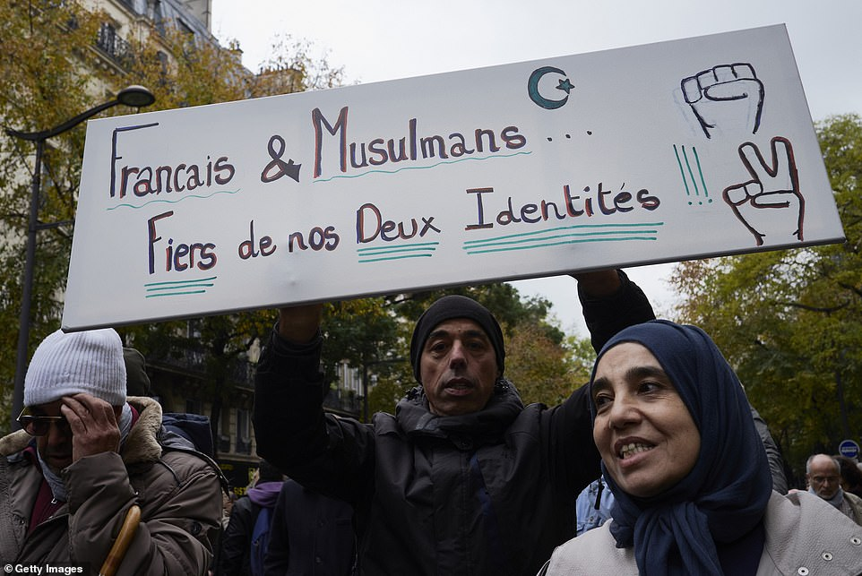 A Muslim man holds a banner reading French And Muslim, Proud Of Both Identities, as an estimated ten thousand French citizens marched from Gare du Nord to Place de la Nation