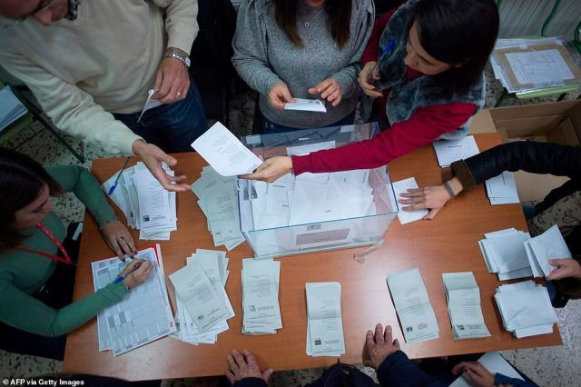 Officials are pictured counting ballot papers at a polling station in Ronda after Spain held general elections on Sunday