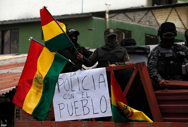 Police against the reelection of now former President Evo Morales are pictured on the rooftop of a police station waving national flags near a sign with a message that reads in Spanish: 'The police is with the people'