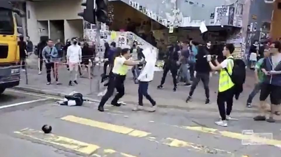 The officer first gets hold of a masked man in a white hooded top, this man later escapes but not before the policeman shoots one of his comrades who attempts to liberate him