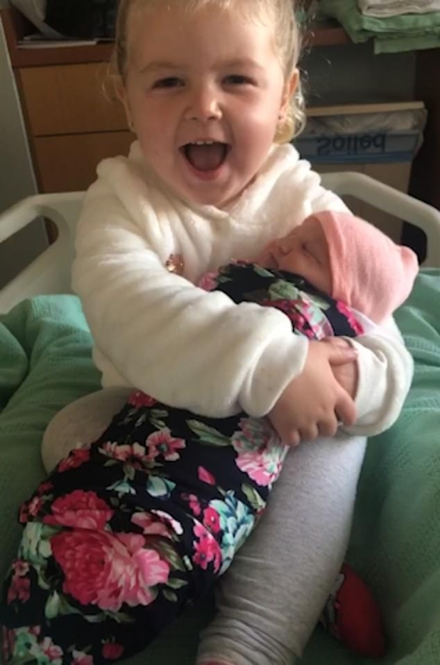 Molly beams with pride as she spends time with her baby sister and tells her mother: 'She's so cute'