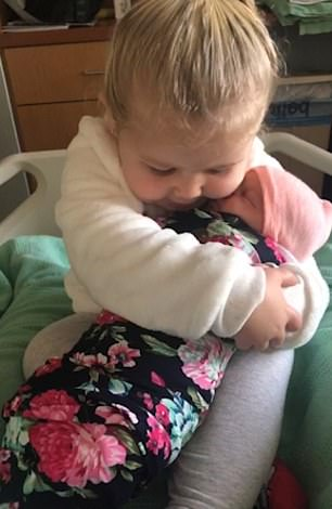 The toddler gives the baby a gently hug as her mother watches on
