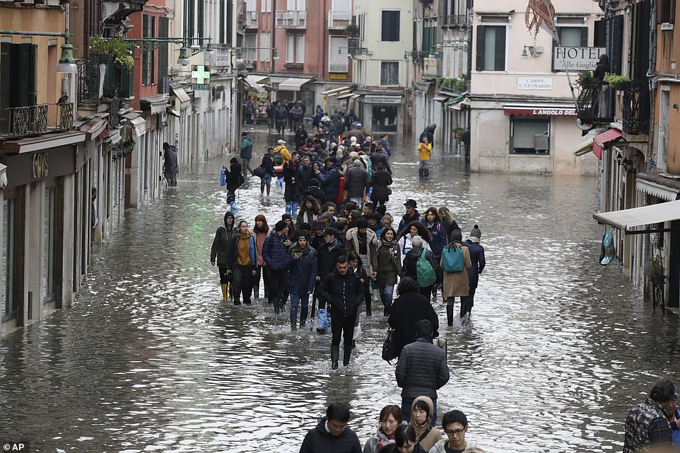 A crowd of people wade through a street in Venice with hotels and shops on either side fearing damage from the flood