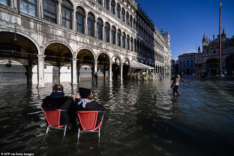 Two people sit on bistro chairs in the middle of flooded St Mark's Square while other chairs are stacked up outside a cafe