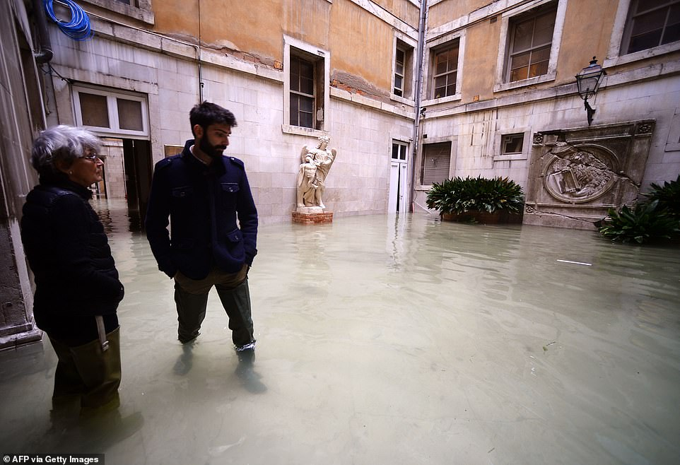 People wearing waterproof gear assess the situation in a building's flooded courtyard in Venice this morning