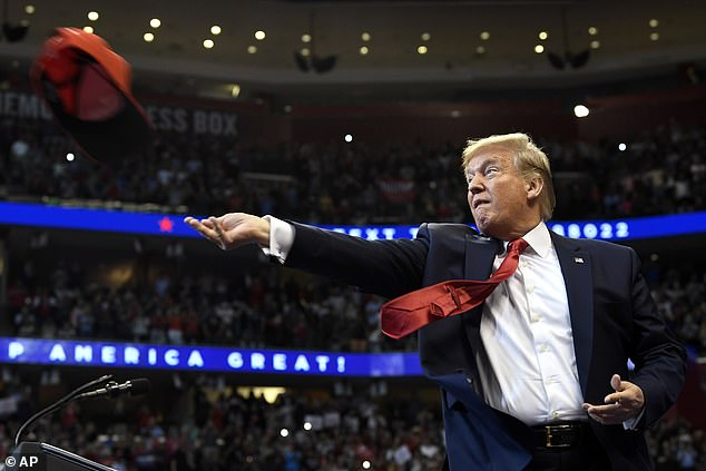 Trump throws 'Make America Great Again' hats to the crowd at his rally in Florida Tuesday night