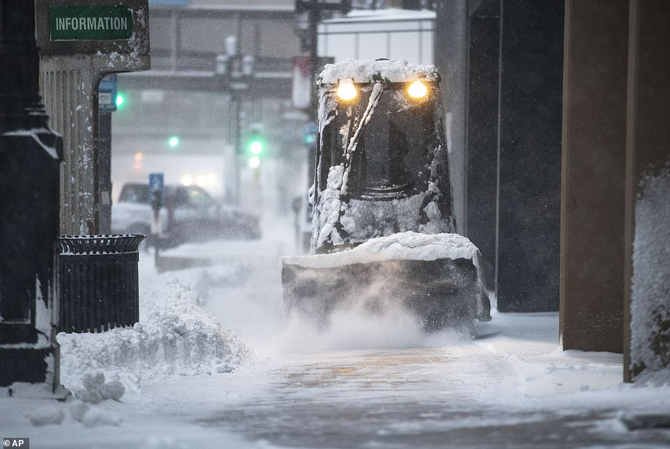 A sidewalk cleaner brushes snow off the sidewalk on Superior Street in Duluth, Minnesota. Cold, blustery and snowy weather produced difficult travel conditions across the United States on Wednesday