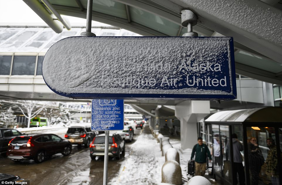 Signage outside Minneapolis-St. Paul International Airport is caked in snow Wednesday after a blizzard struck overnight