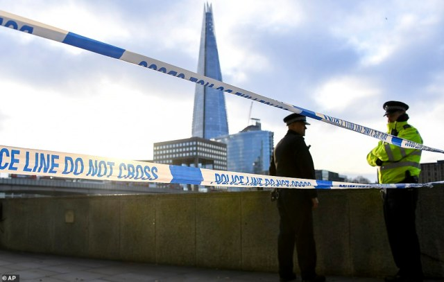 Officers stand behind a police cordon on London Bridge today as investigations continue two days after the terror attack