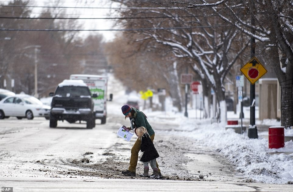 A woman and a child cross the street while battling the weather on a windy and snowy morning in Greeley, Colorado on Saturday. The weather therre caused the city to cancel its annual Greeley Lights the Night parade