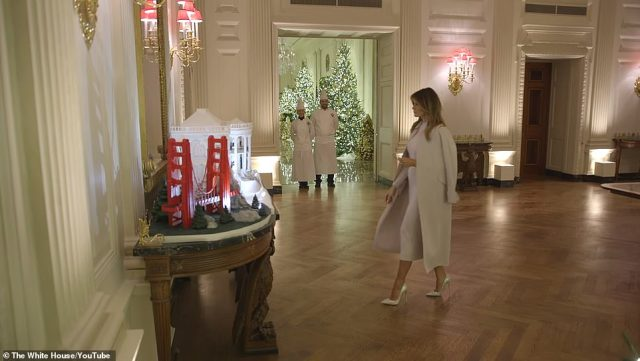 In the clip released Sunday night the first lady can be seen admiring the White House gingerbread house as the bakers look on. The display appears to also incorporate the San Francisco Golden Gate bridge