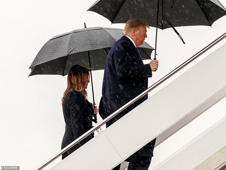 Mr and Mrs Trump board Air force One as they leave Washington DC for London today, both carrying their own separate umbrellas