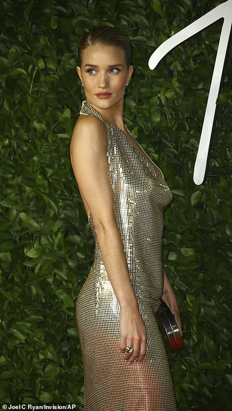 Shine bright:The model, 32, looked sensational in a gold halterneck sequin gown as she joined several famous faces at the glitzy fashion event
