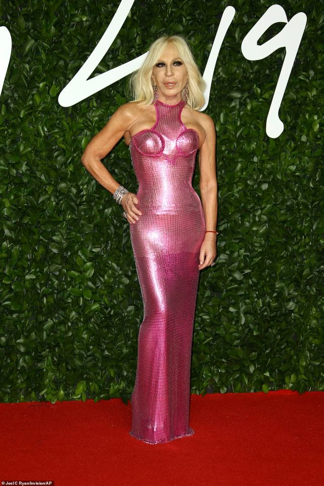 Italian designer Donatella Versace, 64, wore a figure hugging pink dress, paired with matching metallic earrings, cutting a very vibrant figure