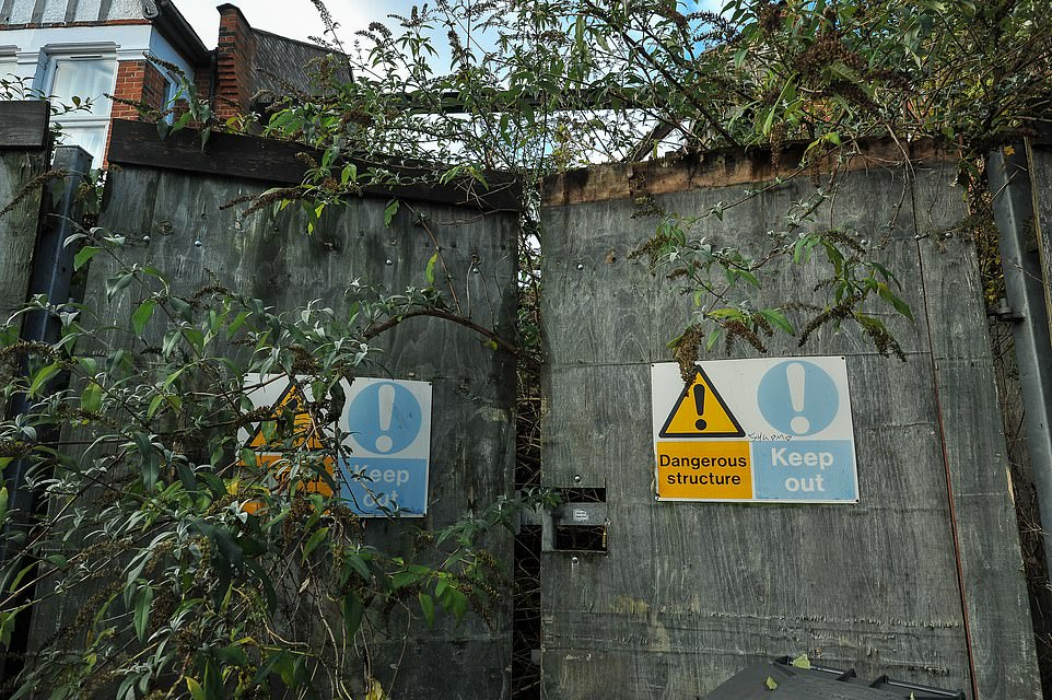 The gaping space is still boarded up and has become overgrown