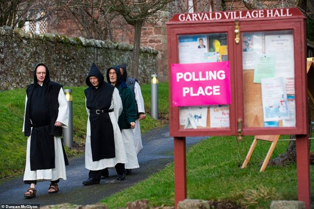 Monks from Nunraw Abbey cast their vote at Garvald Village Hall near Haddington in East Lothian, Scotland