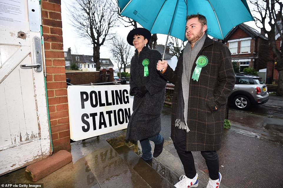 Caroline Lucas (L), Green MP arrives with her son to cast her vote at a polling station in Brighton this morning