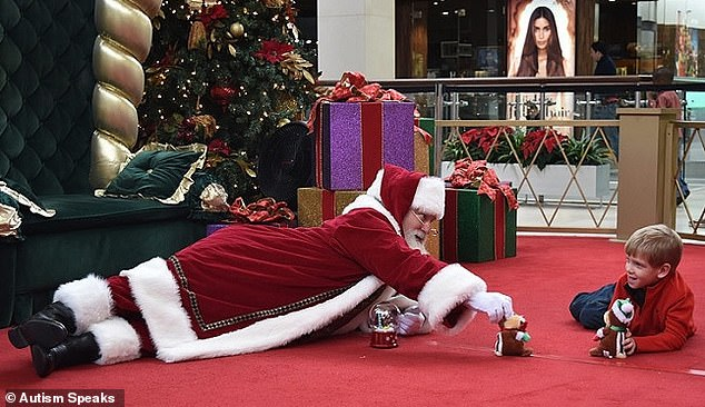 A group has created Santa Cares events in malls across America, geared towards special needs kids. Pictured: A Santa plays with a special needs child