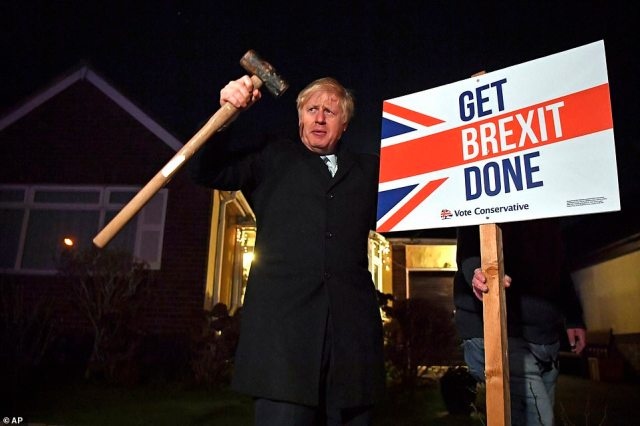 Boris Johnson plants a Get Brexit Done sign in Benfleet, Essex, this evening as he was given a pre-election poll boost putting him on course to win a majority