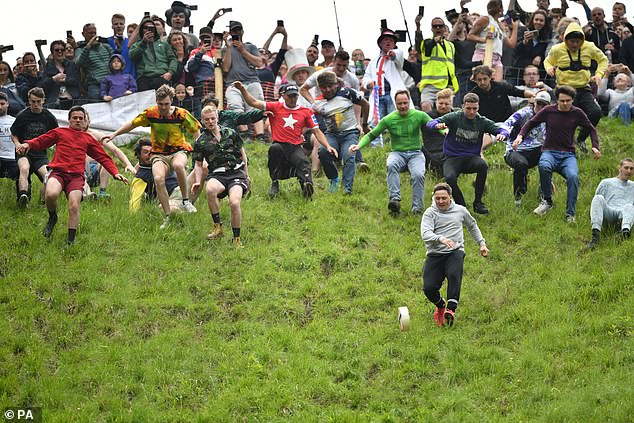 Brave competitors sprint, trip and tumble down Cooper's Hill in an attempt to win the 8lb Double Gloucester