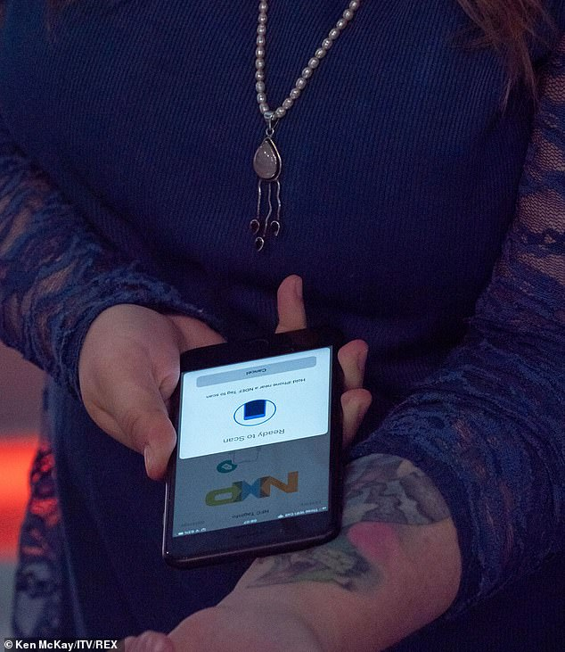 A microchip in her right hand contains her business card information which can be easily transferred with a smartphone (pictured)