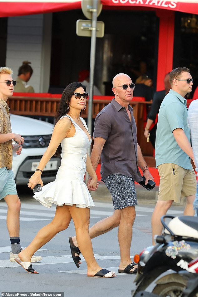 On Monday, Sanchez sported a flirty, white dress with ruffles as Bezos kept it relaxed with multi-print shorts and a dark shirt