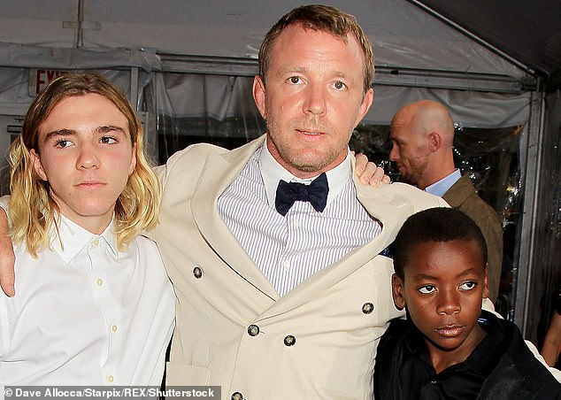 Guy Ritchie is pictured with Rocco Ritchie (left) and David Banda (right) at the premiere of his film The Man from U.N.C.L.E in 2015. On December 23, Ritchie filed a motion in their divorce case asking for the 'enforcement or execution of a judgment or order'