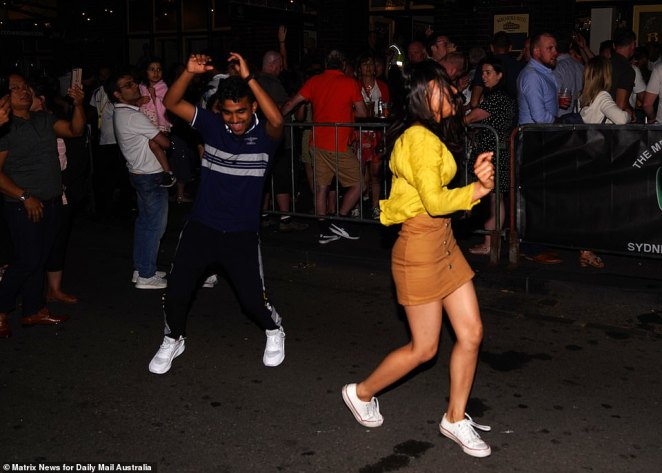 A woman in a yellow top and a burnt orange skirt and white sneakers joined the dance party outside the venue