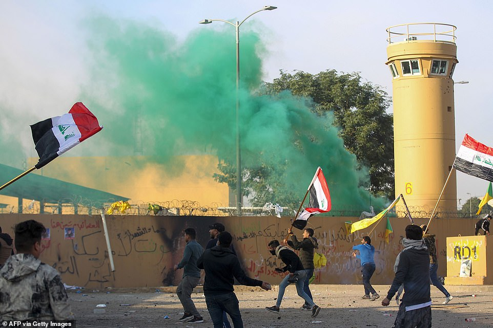 """Supporters and members of the Hashed al-Shaabi paramilitary force gather during a demonstration outside the US embassy in the Iraqi capital Baghdad on Wednesday. They marched unimpeded through the checkpoints of the usually high-security Green Zone to the embassy gates, where they broke through a reception area, chanting """"Death to America"""" and scribbling pro-Iran graffiti on the walls"""