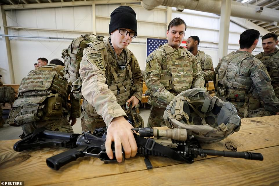 Paratroopers secure their gear and weapons as they prepare to deploy from Fort Bragg on Wednesday