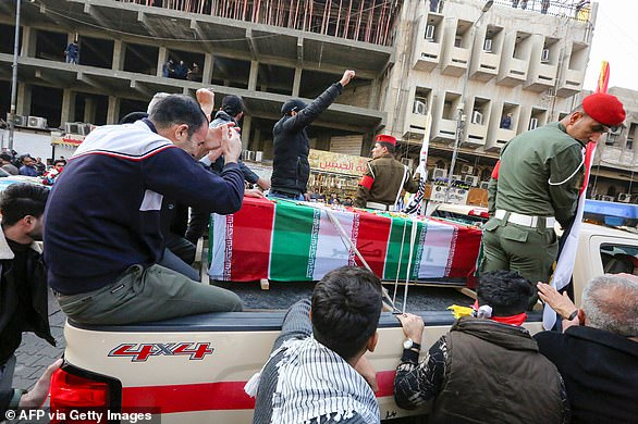 Mourners surround a car carrying the coffin of Iranian military commander Qassem Soleimani through the streets of Baghdad on Saturday