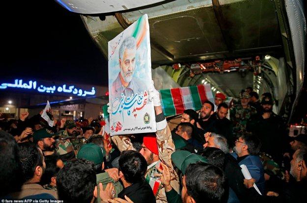 """Ciało Soleimani wróciło do Iranu w niedzielę.  Po przybyciu na międzynarodowe lotnisko Ahvaz w Teheranie widać ludzi niosących jego trumnę.  Szkatułę przywitały okrzyki """"Śmierci Ameryce"""", gdy Iran wydał nowe groźby odwetu"""