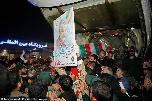 Soleimani's body was returned to Iran on Sunday. People are seen carrying his casket upon arrival at Ahvaz International Airport in Tehran. The casket was greeted by chants of 'Death to America' as Iran issued new threats of retaliation