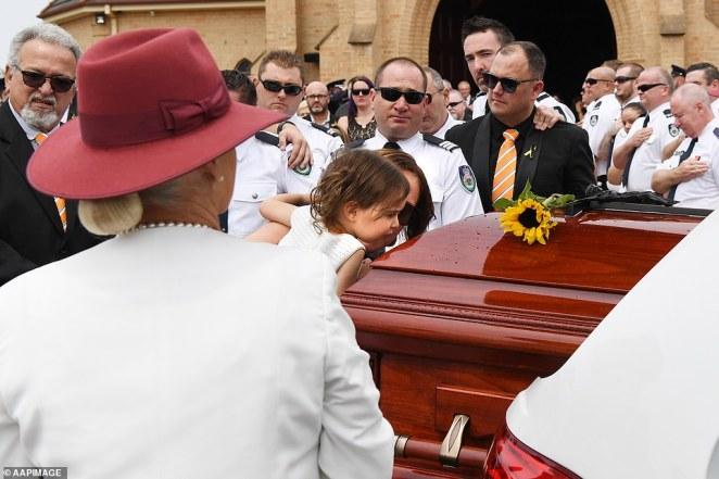 Outside the service, Melissa O'Dwyer carried carried Charlotte in her arms before lowering her down so she could give her hero father's coffin a kiss goodbye. Around her, eyes welled with tears.