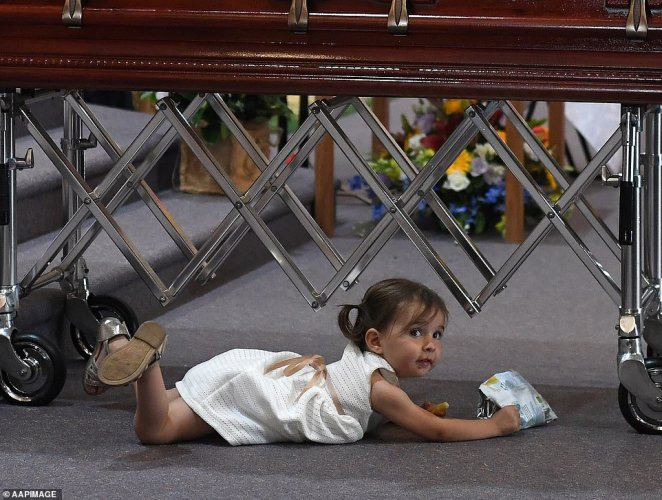 At one point, Mr O'Dwyer's young daughter lay on the floor under his coffin eating from a bag of chips, with her innocence bringing a smile to the face of the mourners packed into the church