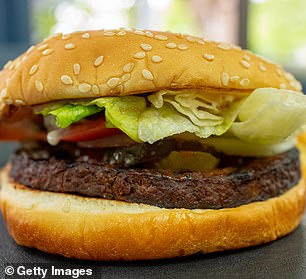 Close-up of vegan high-tech, plant-based burger using engineered soy proteins, potato proteins and plant-derived fats, on a bun with onions, lettuce, and tomato, on a table in a fast food setting