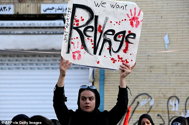 A woman holds up a placard declaring 'we want revenge' during today's funeral gathering in Soleimani's home town