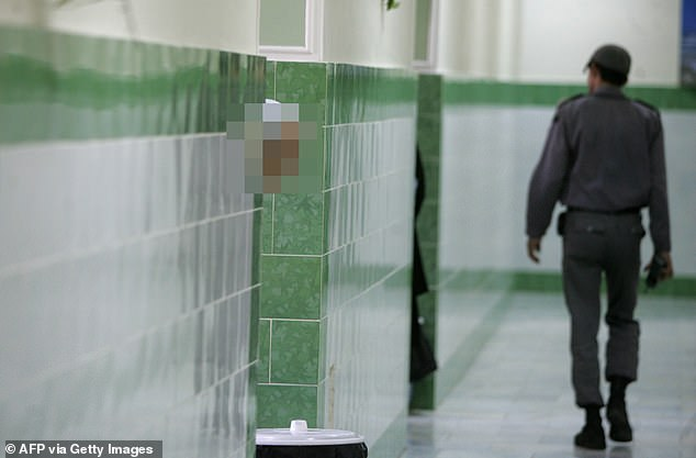 Pictured: Inside a corridor of the notorious Evin prison in Tehran as a guard monitors the halls