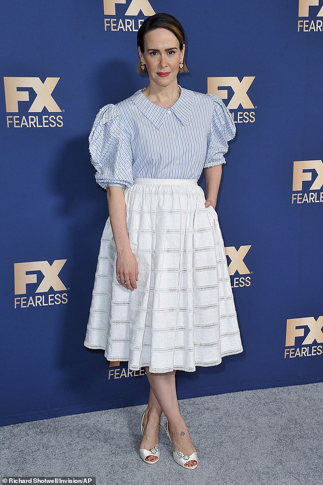 Classy: Paulson, 45, opted for a blue striped blouse and a white broderie anglaise knee-length skirt. She paired the ensemble with white peep toe heels and a pair of heart-shaped earrings