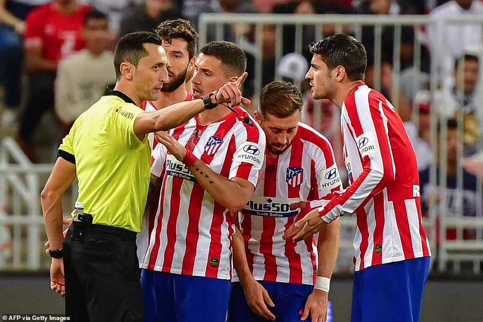 Atletico Madrid players try to talk to referee Jose Maria Sanchez Martinez after a decision has gone differently